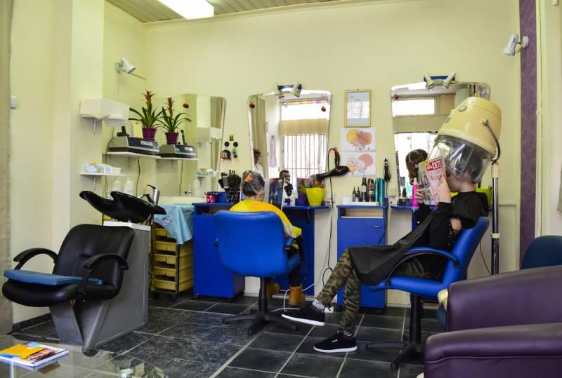 Slika lokala sa dve mušterije koje sede u stolicama i čitaju novine